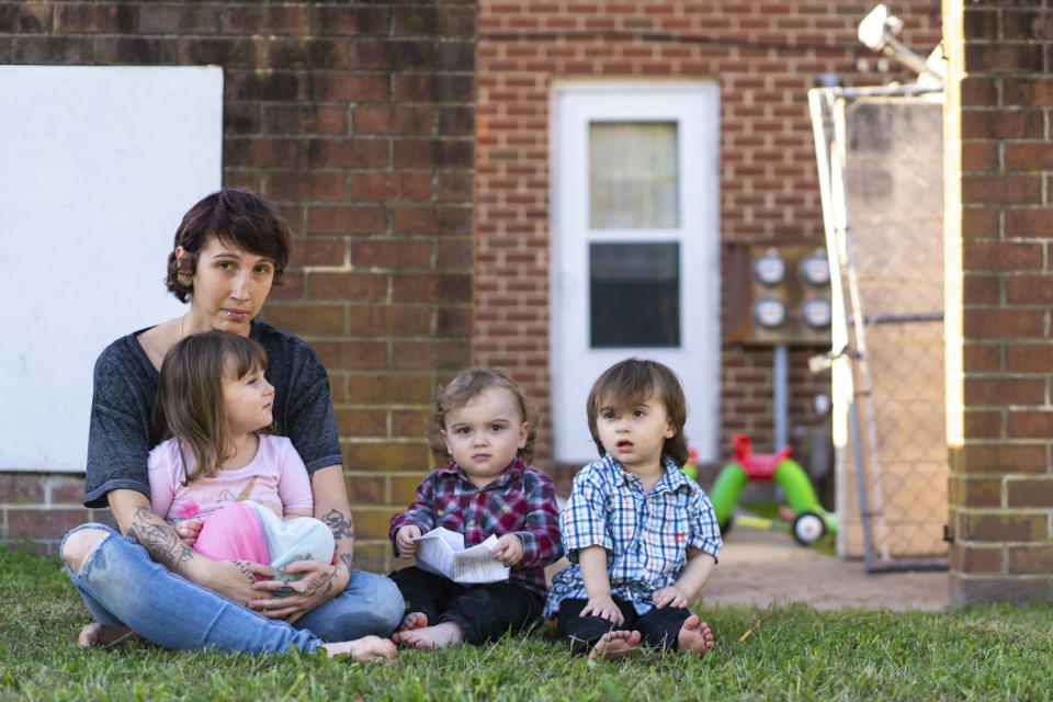 Kandise Norris, shown here with her three children in a Nov. 7 photo outside their home in Somerset County, Maryland, says she has been rebuilding her life since getting treatment for drug addiction in April 2019. The Housing Authority of Crisfield, Maryland, which owns her house, has filed three eviction cases against the 30-year-old since September. (Nick McMillan/Howard Center for Investigative Journalism via AP)