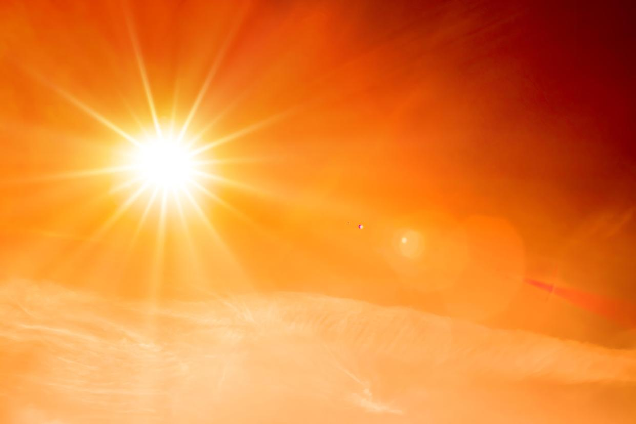 Orange sky with bright sun symbolizing climate change and global warming