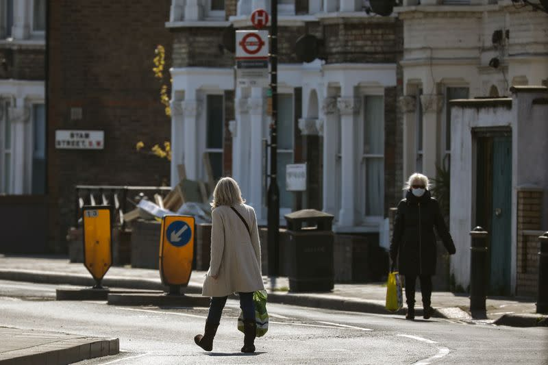 Women with shopping bags walk on a deserted residential street in London