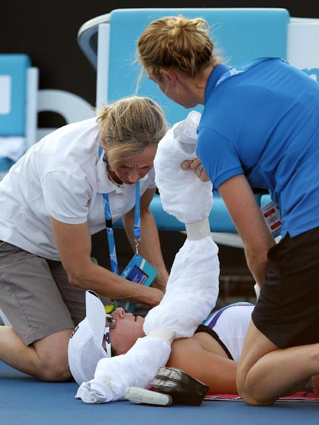 Yaroslava Shvedova of Kazakhstan receives treatment by trainers during her first round match against Sloane Stephens of the U.S. at the Australian Open tennis championship in Melbourne, Australia, Tuesday, Jan. 14, 2014