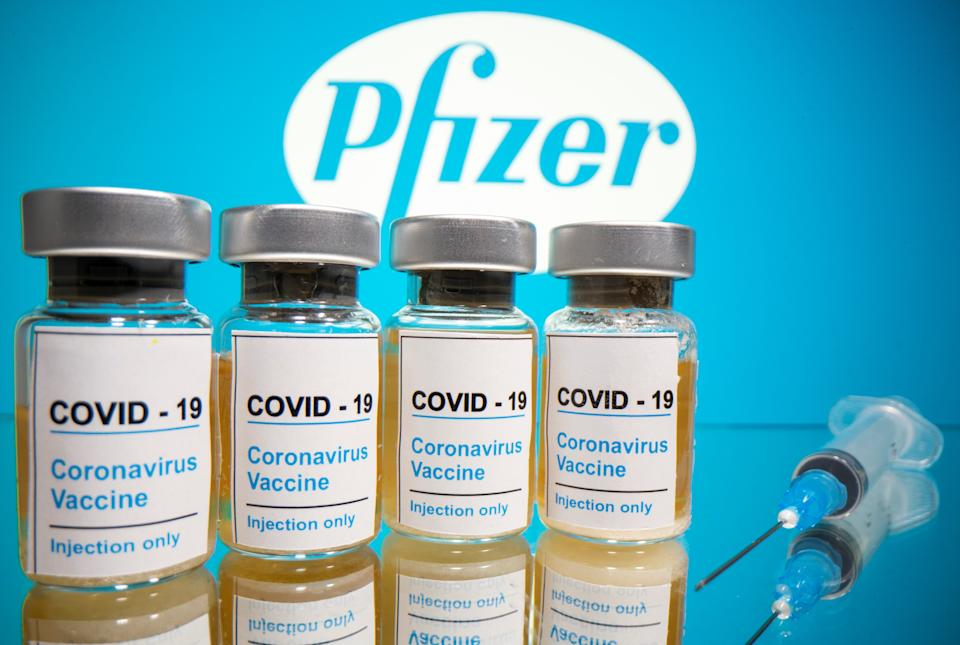 """Vials with a sticker reading, """"COVID-19 / Coronavirus vaccine / Injection only"""" and a medical syringe are seen in front of a displayed Pfizer logo in this illustration taken October 31, 2020. REUTERS/Dado Ruvic/Illustration"""