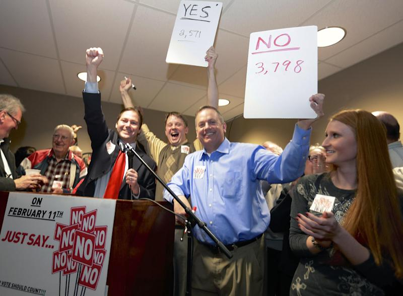 State Sen. Charlie Jansssen of Fremont, third left, Jeremy Jensen, center, and John Wiegert, second right, celebrate in Fremont, Neb., Tuesday, Feb. 11, 2014, after city voters have decided by voting no, to uphold the law designed to bar immigrants from renting homes if they don't have legal permission to be in the U.S. (AP Photo/Nati Harnik)