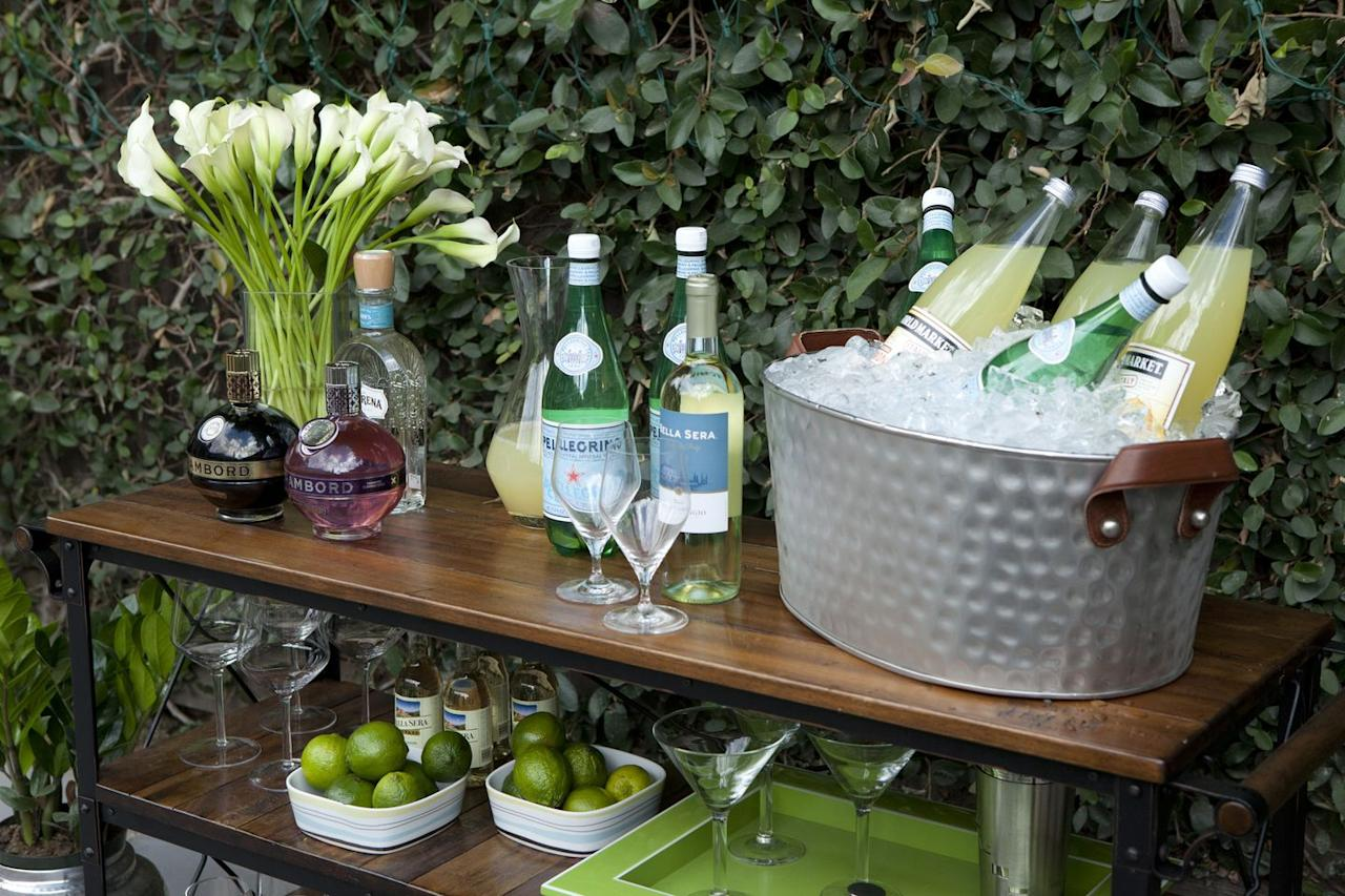 <p>Don't be afraid to mix and match various martini glasses and wine decanters that you are able to find. Tying them together on an old cart or platter will give your backyard a chic, Pottery Barn look for a fraction of the cost. </p>