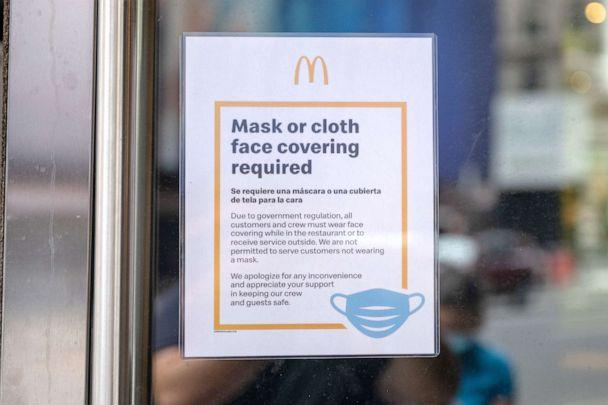 PHOTO: A 'Mask or cloth face covering required' sign is displayed at the entrance of a McDonald's near Times Square as the city continues Phase 4 of re-opening following restrictions imposed to slow the spread of coronavirus, July 24, 2020, in New York. (Alexi Rosenfeld/Getty Images)
