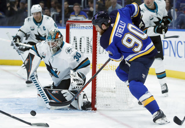 St. Louis Blues' Ryan O'Reilly (90) tries to get off a shot as San Jose Sharks goaltender Aaron Dell (30) defends during the second period of an NHL hockey game Friday, Nov. 9, 2018, in St. Louis. (AP Photo/Jeff Roberson)