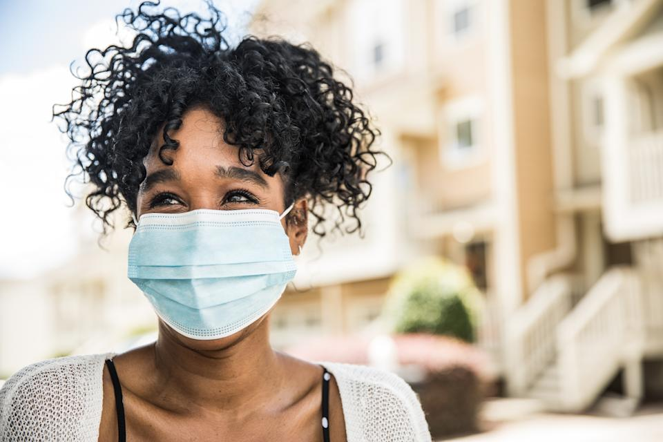 Young woman wearing surgical mask in front of home