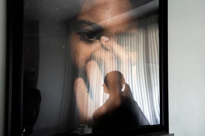 Karen Robinson is reflected in a portrait of her late daughter, Jasmine Lewis, at her home in North Philadelphia.