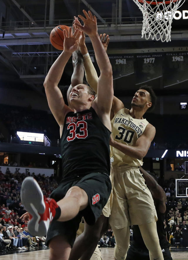 North Carolina State's Wyatt Walker (33) and Wake Forest's Olivier Sarr (30) compete for a rebound during the first half of an NCAA college basketball game in Winston-Salem, N.C., Tuesday, Jan. 15, 2019. (AP Photo/Chuck Burton)