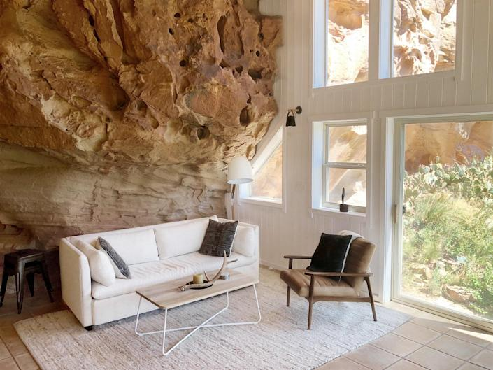 """Appropriately named the Cliff House, this Mid-Century-inspired bungalow is built right into a red rock wall of a canyon alcove in Cortez, Colorado. And just around the corner from the house, in another rocky niche, is a lawn outfitted with comfortable porch seating for al fresco cocktail hours. One feature—or lack that of—to note is the absence of televisions. The homeowners are such fans of the surrounding desert that they opted out of screens altogether to be more in the moment when spending time in the Cliff House. There is, however, ultra-high-speed Wifi so that guests don't have to sacrifice missing the latest episode of their favorite shows or an important email. $298, Airbnb. <a href=""""https://www.airbnb.com/rooms/33513388?"""" rel=""""nofollow noopener"""" target=""""_blank"""" data-ylk=""""slk:Get it now!"""" class=""""link rapid-noclick-resp"""">Get it now!</a>"""