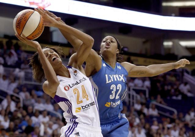 Phoenix Mercury's DeWanna Bonner (24) tries to shoot as Minnesota Lynx's Rebekkah Brunson (32) defends during the first half of a WNBA Western Conference Finals basketball game on Sunday, Sept. 29, 2013, in Phoenix. (AP Photo/Ross D. Franklin)