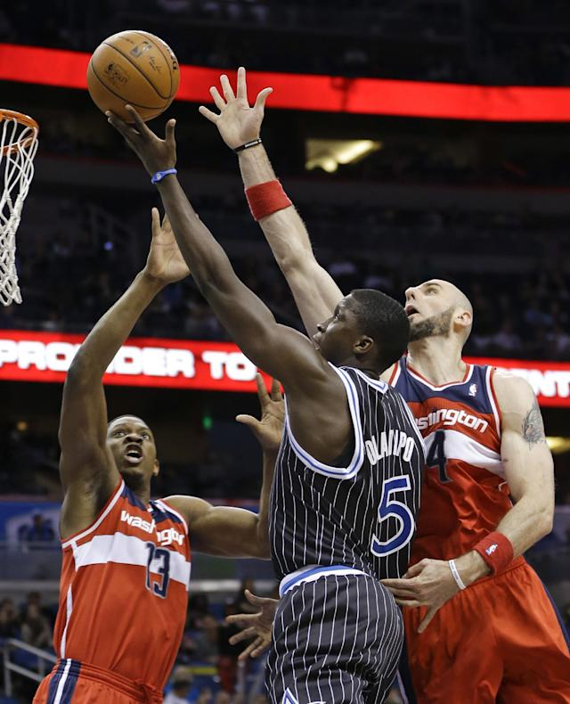 Orlando Magic's Victor Oladipo (5) takes shot as Washington Wizards' Bradley Beal (3) and Marcin Gortat, right, defend during the second half of an NBA basketball game in Orlando, Fla., Friday, March 14, 2014. Washington won in overtime, 105-101. (AP Photo/John Raoux)
