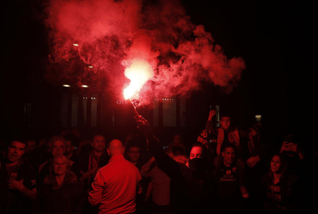 A FC Barcelona supporter burns a flare as he celebrates Barcelona's victory in the Spanish league title at Canaletas source at Las Ramblas in Barcelona, Spain, Sunday, April 29, 2018. (AP Photo/Manu Fernandez)