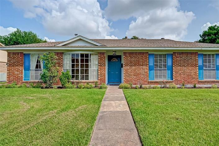 The exterior of the house for sale in Houston with a lawn out front and a blue door