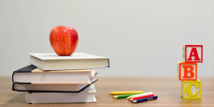 A stack of books with an apple on top, next to color pencils and a stack of alphabet blocks.