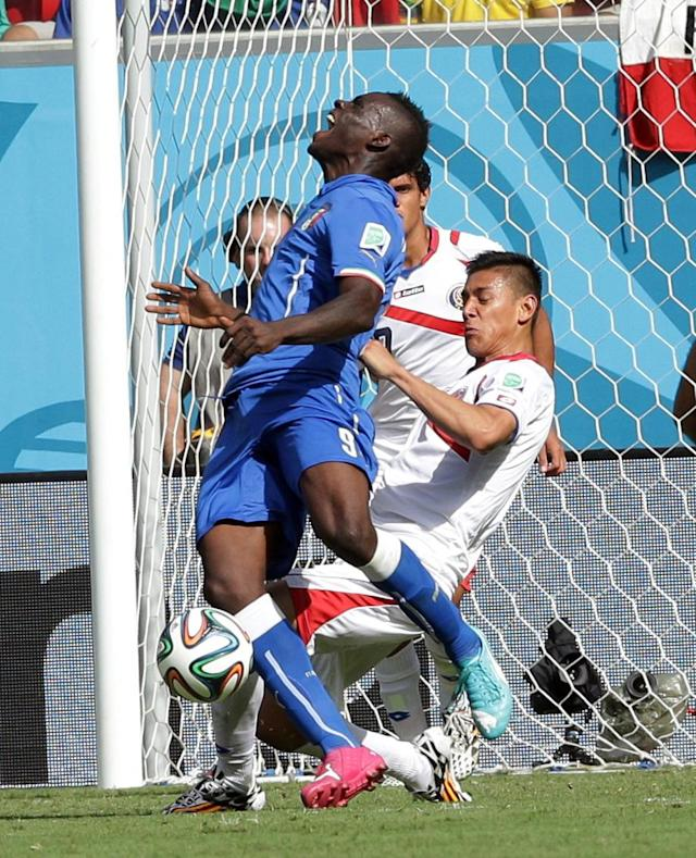 Italy's Mario Balotelli, left, claims a penalty after a challenge from Costa Rica's Oscar Duarte during the group D World Cup soccer match between Italy and Costa Rica at the Arena Pernambuco in Recife, Brazil, Friday, June 20, 2014. No penalty was awarded. (AP Photo/Antonio Calanni)
