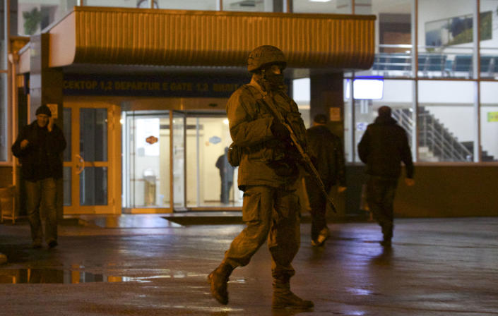 An unidentified armed man patrols a square in front of the airport in Simferopol, Ukraine, Friday, Feb. 28, 2014. Dozens of armed men in military uniforms without markings occupied the airport in the capital of Ukraine's strategic Crimea region early Friday. (AP Photo/Ivan Sekretarev)