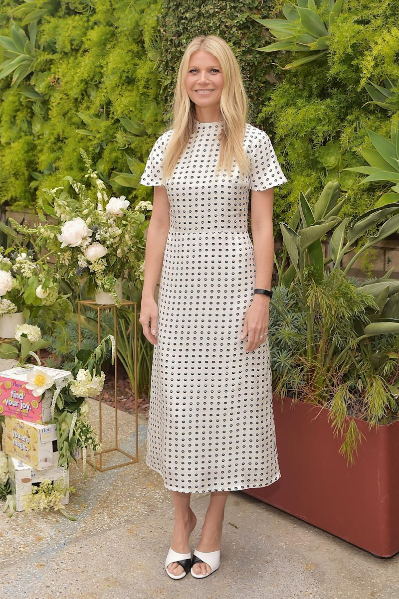 Gwyneth Paltrow looks incredible in this white dress with black dots all over it and a pair or white and black mule