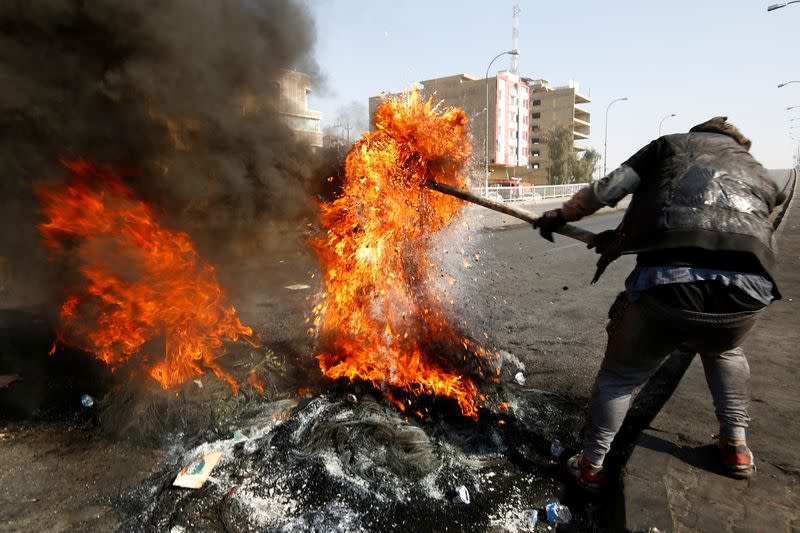 An Iraqi demonstrator burns tires to block a road during ongoing anti-government protests in Najaf,