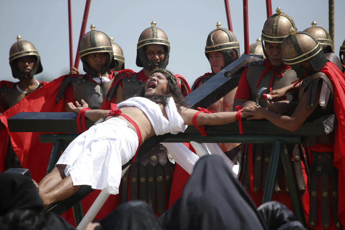 Filipino penitent Ruben Enaje, who has portrayed as Jesus Christ for 27 times, grimaces as he is nailed to the cross during Good Friday rituals on March 29, 2013 at Cutud, Pampanga province, northern Philippines. Several Filipino devotees had themselves nailed to crosses Friday to remember Jesus Christ's suffering and death, an annual rite rejected by church leaders in this predominantly Roman Catholic country. (AP Photo/Aaron Favila)