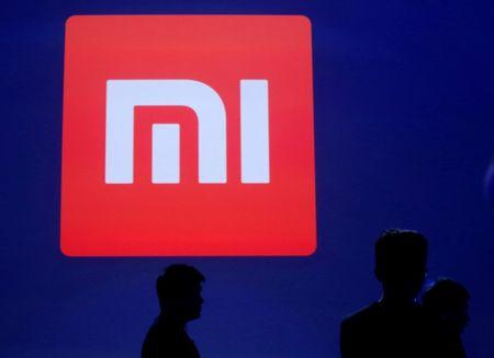 Attendants are silhouetted in front of Xiaomi's logo in Beijing
