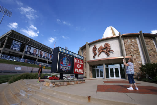 FILE - In this Aug. 7, 2015, file photo, a visitor to the Pro Football Hall of Fame pauses to take a photo of the sign in front in Canton, Ohio. The NFL has canceled the Hall of Fame game that traditionally opens the preseason and is delaying the 2020 induction ceremonies because of the coronavirus pandemic, two people with direct knowledge of the decision told The Associated Press on Thursday, June 25, 2020. The people spoke to the AP on condition of anonymity because the decision has not been publicly announced, though an announcement is expected later Thursday. (AP Photo/Gene J. Puskar, File)