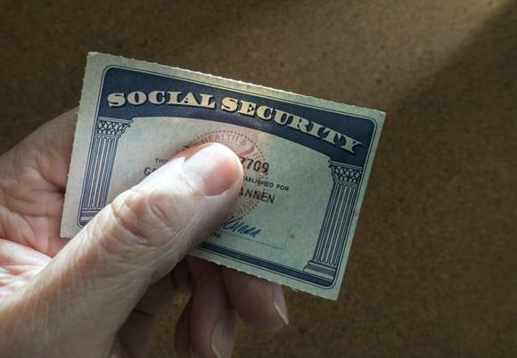 A senior's hand tightly holding a Social Security card.