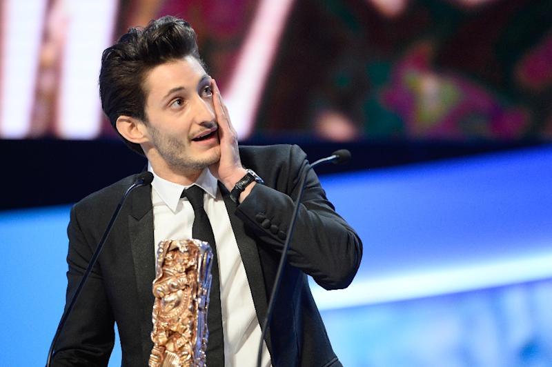 """French actor Pierre Niney accepts the Best Actor award for his role in """"Yves Saint Laurent"""" at the Cesar Awards ceremony on February 20, 2015 in Paris (AFP Photo/Bertrand Guay)"""