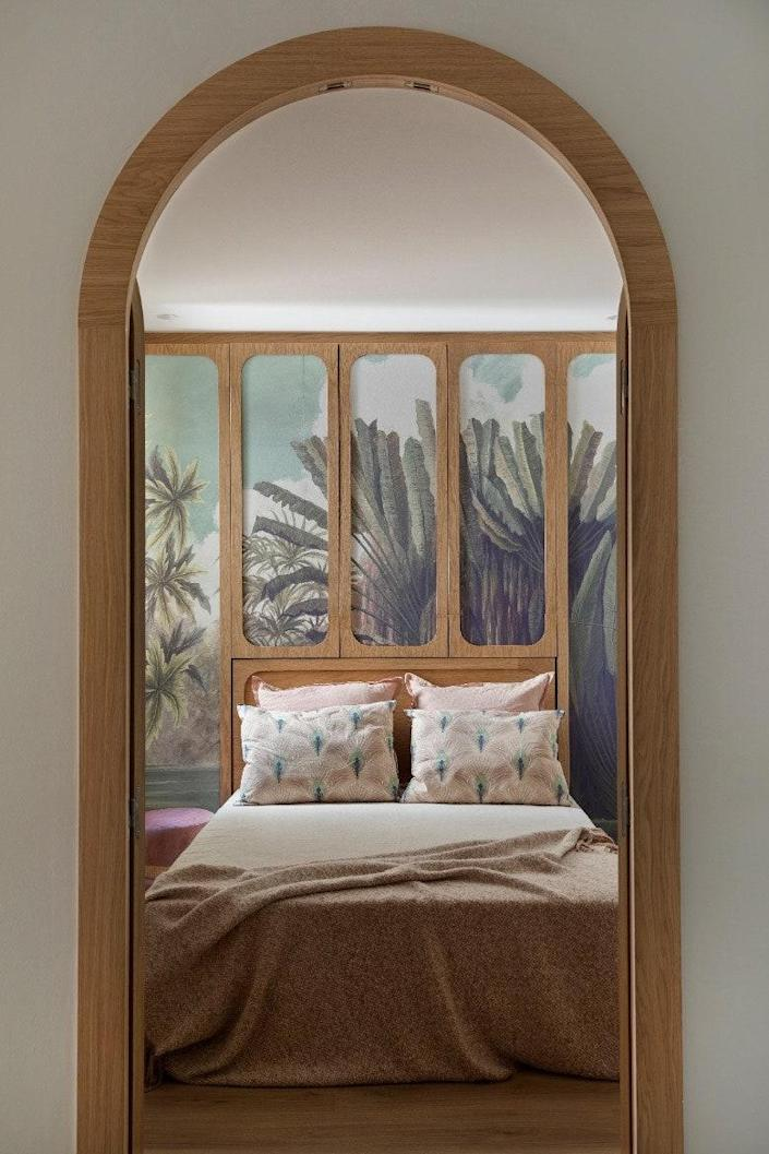 The tropical wallpaper by Ananbô contrasts with the wooden doors by Noé Prades Studio.