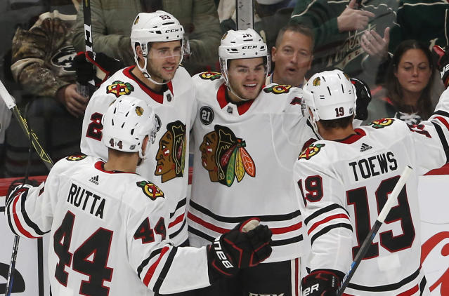 Chicago Blackhawks' Alex DeBrincat, second from right, is congratulated by teammates after scoring against Minnesota Wild goalie Devan Dubnyk during the first period of an NHL hockey game Thursday, Oct. 11, 2018, in St. Paul, Minn. (AP Photo/Jim Mone)