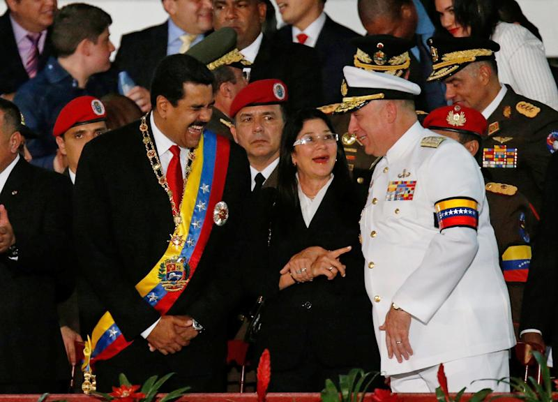 Venezuela's President Nicolas Maduro, left, speaks with Defense Minister Admiral Diego Molero, right, during an Independence Day parade at Fort Tiuna in Caracas, Venezuela, Friday, July 5, 2013. Standing at center is Venezuela's first lady Cilia Flores. The presidents of Venezuela and Nicaragua offered Friday to grant asylum to NSA leaker Edward Snowden, one day after leftist South American leaders gathered to denounce the rerouting of Bolivian President Evo Morales' plane over Europe amid reports that the American was aboard. (AP Photo/Fernando Llano)