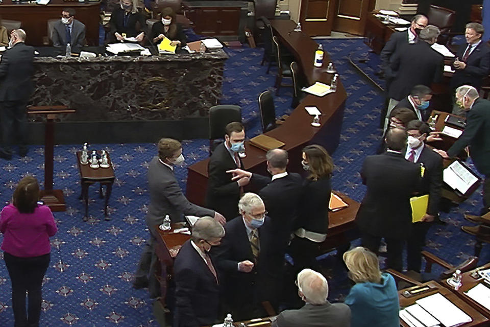 In this image from video, Senate Minority Leader Mitch McConnell of Ky., lower center right, and other Republican senators and staff talk on the floor after a vote on the motion to allow witnesses in the second impeachment trial of former President Donald Trump in the Senate at the U.S. Capitol in Washington, Saturday, Feb. 13, 2021. (Senate Television via AP)