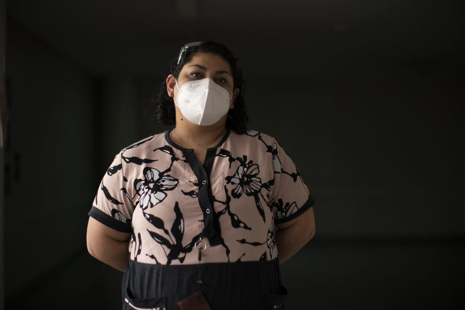 Paola Almiron, a nursing supervisor poses for a photo at the Luisa Cravenna de Gandulfo Interzonal General Hospital in Lomas de Zamora, south of Buenos Aires, Argentina, Friday, July 9, 2021. Almiron was hospitalized last year with COVID-19 and survived. Her mother, sister, aunt and brother-in-law died of the disease. (AP Photo/Victor R. Caivano)