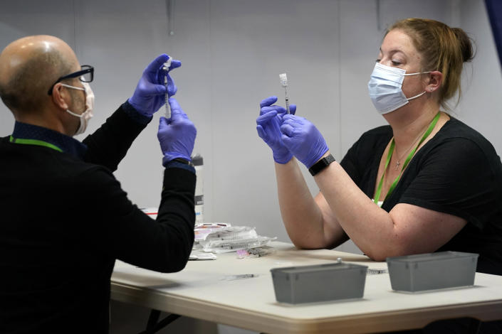 Nick Bloom, left, and Hollie Maloney, pharmacy technicians, fill syringes with Pfizer's COVID-19 vaccine, Tuesday, March 2, 2021, at the Portland Expo in Portland, Maine. The Expo location, operated by Northern Light Health, is one of two mass vaccination sites that opened in Maine this week. (AP Photo/Robert F. Bukaty)