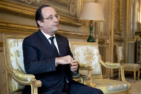 French President Hollande reacts during a meeting with a guest in his office at the Elysee Palace in Paris