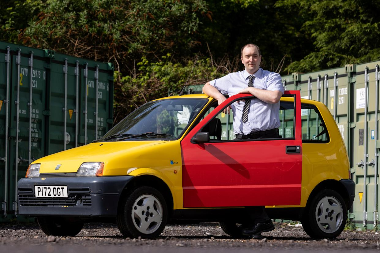 Auctioneer Andy Stowe with the famous yellow Fiat Cinquecento from the Inbetweeners TV show which is coming up for auction at East Bristol Auctions. (SWNS)