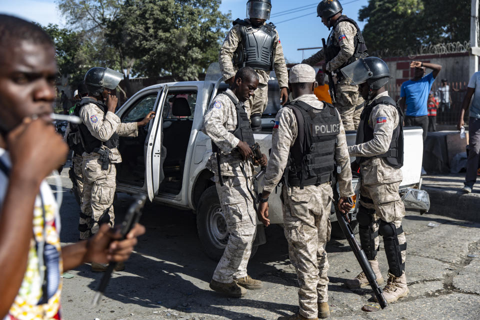 Haitian police officers load their riot guns before firing tear gas canisters toward the groups of protesters who were marching toward the U.S. Embassy. (Photo by Adam DelGiudice/SOPA Images/LightRocket via Getty Images)