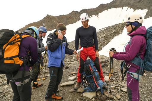 A French gendarme confirms by telephone a hut reservation for a group of climbers before allowing them to start toward the Mont Blanc, the highest peak in Europe