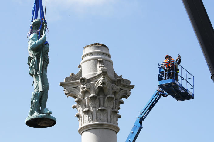 Crews remove the Confederate Soldiers & Sailors Monument in Libby Hill Park, Wednesday, July 8, 2020, in Richmond, Va. The 17 ft statue stands on a 73 foot pedestal overlooking downtown. The statue is one of several that will be removed by the city as part of the Black Lives Matter reaction. (AP Photo/Steve Helber)