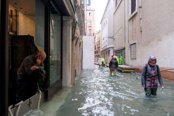 PHOTO: People walk in the flooded street during a period of seasonal high water in Venice, Italy, Nov. 15, 2019. (Manuel Silvestri/Reuters)
