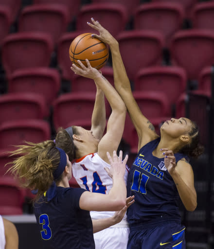 Boise State guard Braydey Hodgins (14) has a shot blocked by Nevada forward Terae Briggs (11) during the last quarter of an NCAA college basketball women's championship game in the Mountain West Conference tournament Friday, March 9, 2018, in Las Vegas. (AP Photo/L.E. Baskow)