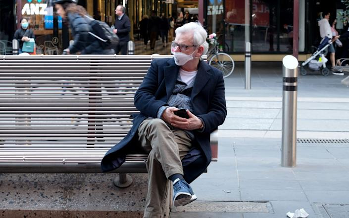 A man wearing a face mask sits on a bench prior to the general lockdown in Melbourne, Victoria. - Luis Ascui/EPA-EFE/Shutterstock