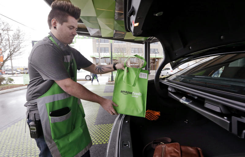 An Amazon worker, who declined to be identified, loads a bag of groceries into a customer's car trunk at an AmazonFresh Pickup location, Tuesday, March 28, 2017, in Seattle. Amazon began testing the new grocery pickup service, currently open only to Amazon employees, Tuesday in Seattle. Eventually, members of Amazon's $99-a-year Prime loyalty program will be able to order groceries online and drive to a pickup location at a scheduled time, where crews will deliver items to the car. Amazon says orders will be ready in as few as 15 minutes after being placed. (AP Photo/Elaine Thompson)