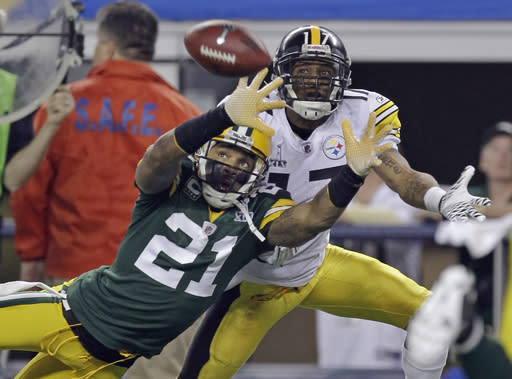 FILE - In this Feb. 6, 2011, file photo, Green Bay Packers' Charles Woodson (21) breaks up a pass intended for Pittsburgh Steelers' Mike Wallace during the first half of the NFL football Super Bowl XLV football game in Arlington, Texas. Woodson, in his first-year of eligibility, was selected as a finalist for the Pro Football Hall of Fame's class of 2021 on Tuesday, Jan. 5, 2021. (AP Photo/Dave Martin, File)