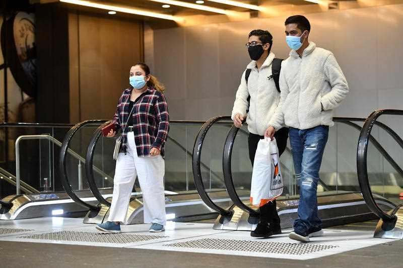 Commuters wearing face masks uses leaves Wynyard Station in Sydney.