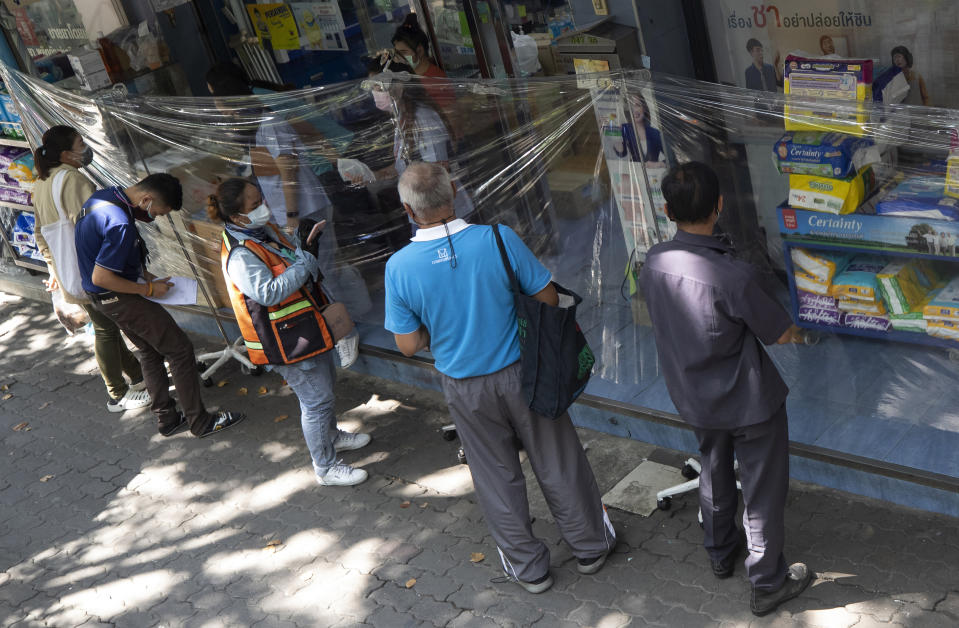 Customers wearing protective masks to help curb the spread of the coronavirus order medicine through plastic sheets front of drug store in Bangkok, Thailand, Thursday, May 27, 2021. (AP Photo/Sakchai Lalit)