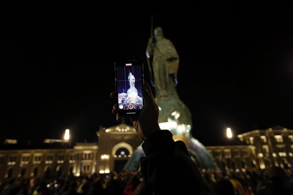A man takes a video of a 23-meter-high, 70-ton bronze sculpture of the legendary founder of the Serbian state, Stefan Nemanja, during the unveiling ceremony in Belgrade, Serbia, Wednesday, Jan. 27, 2021. President Aleksandar Vucic's allies say the bronze sculpture of Stefan Nemanja will be a new landmark of the Serbian capital. Opponents think the monument is a megalomaniac and pricy token of Vucic's populist and autocratic rule that should be removed. (AP Photo/Darko Vojinovic)