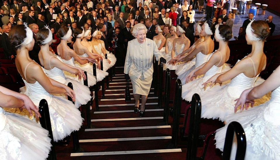 <p>Queen Elizabeth ascends a staircase lined with ballerinas while visiting the Royal Albert Hall in 2004.</p>