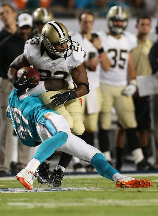 Miami Dolphins safety Kelcie McCray (37) tackles New Orleans Saints running back Pierre Thomas (23) during the first half of an NFL preseason football game, Thursday, Aug. 29, 2013, in Miami Gardens, Fla. (AP Photo/J Pat Carter)