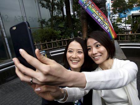 Hiroko Masuhara (L) and her partner Koyuki Higashi take 'selfie' pictures in front of the statue of famous Japanese dog Hachiko after the ward office issued the nation's first same sex partnership certificates in Tokyo, Japan, November 5, 2015.REUTERS/Yuya Shino