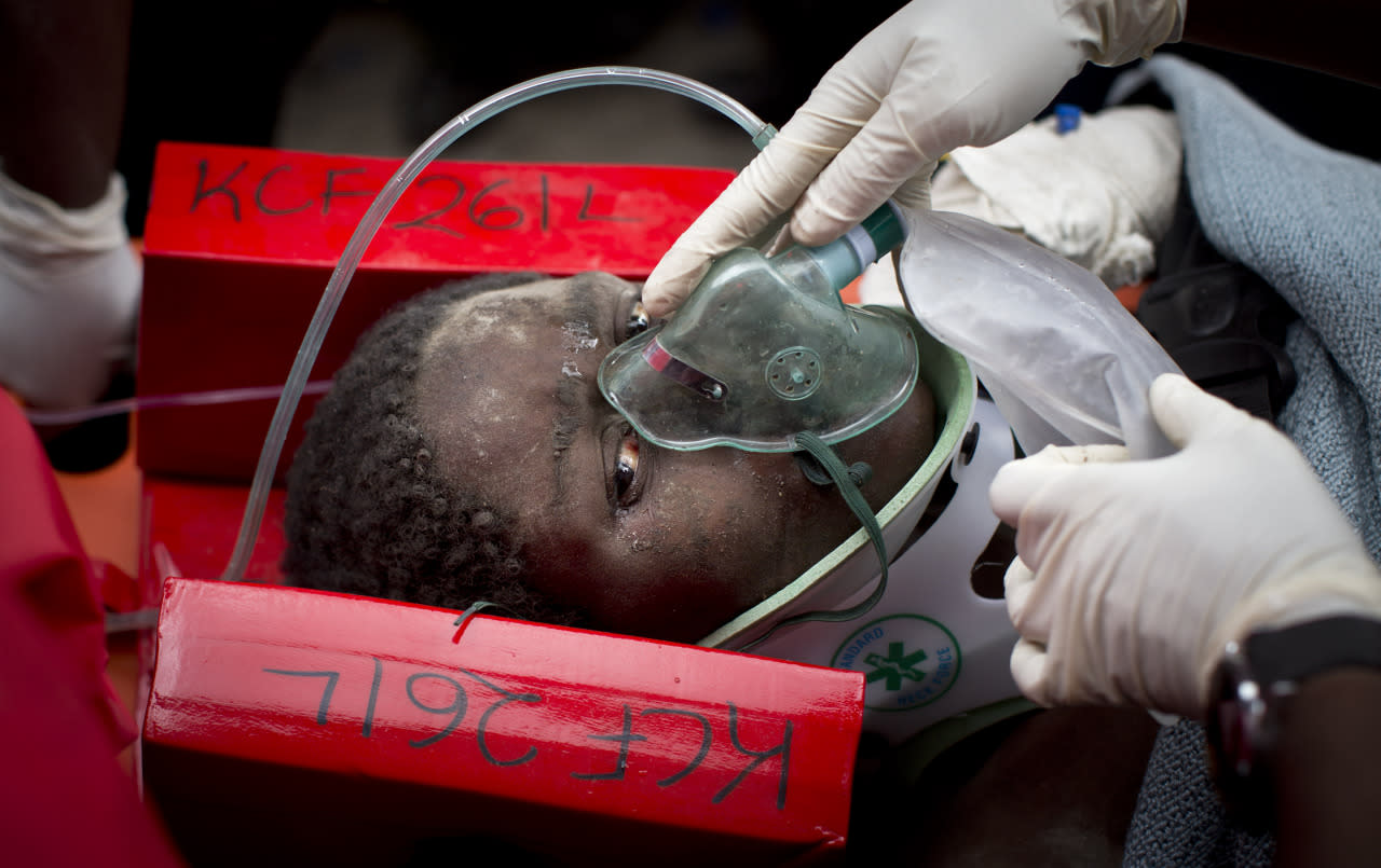 A woman is carried away in a stretcher by medics as she is rescued after being trapped for six days in the rubble of a collapsed building, in the Huruma area of Nairobi, Kenya, May 5, 2016. After discovering the woman alive and conscious, rescuers administered an IV and oxygen but then had to work for a number of hours to free her from the rubble she was trapped in, before taking her away to hospital. (Ben Curtis/AP)